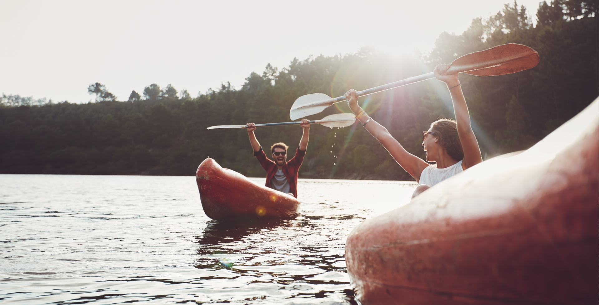 boy and girl on kayaks holding their paddles up high