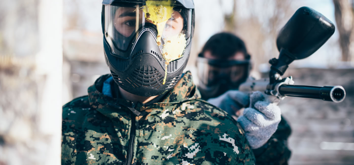 photo of a paintball player with a yellow paint splash on his mask