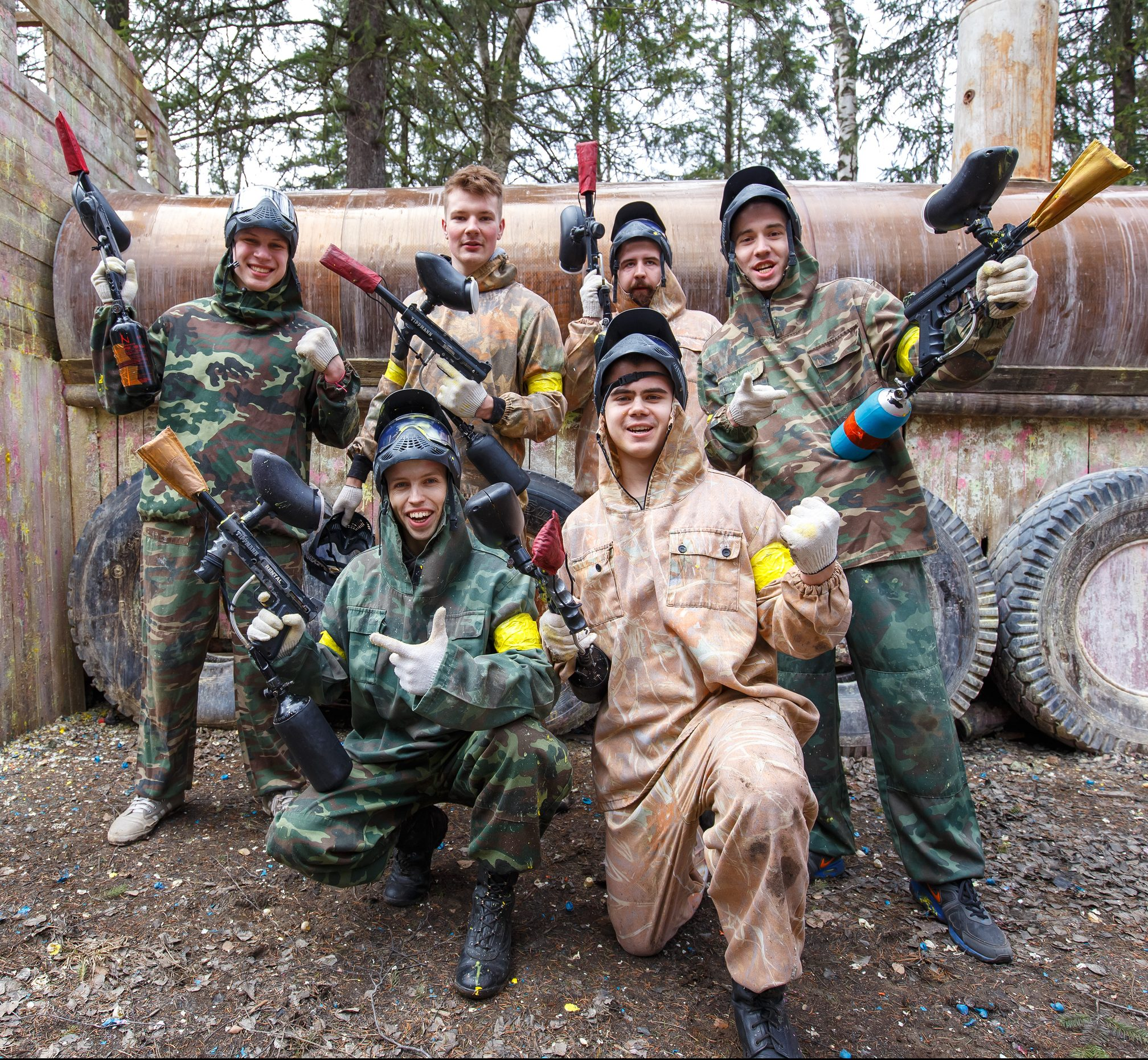 group of friends posing with paintball markers and equipment